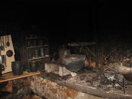 Črna kuhinja s kuriščema, kotlom obešenim na ciganu in delom kuhinjskega orodja