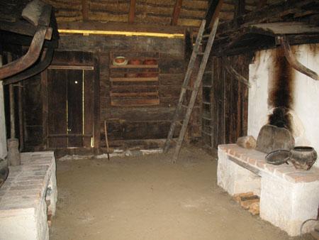 Črna kuhinja z dvema ognjiščema in lesenima obokoma nad obema