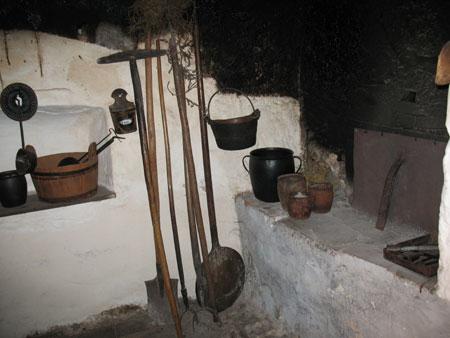 Črna kuhinja s posodami in kuhinjskim orodjem.