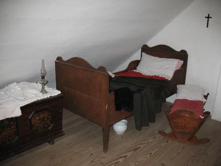 Kamra s posteljo, zibko in skrinjo.