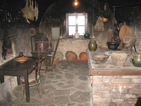 Obokana črna kuhinja z zidanim kuriščem za kuhanje.