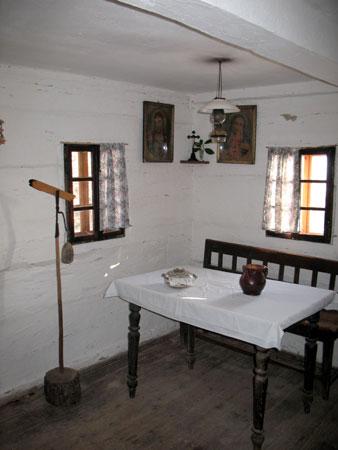 Bogkov kot z mizo, klopjo in čelesnikom v bivalnem prostoru (hiši)