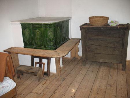 Pri peči v hiši stoji stara lesena skrinja, ki je izdelana izključno iz lesa (brez žebljev)