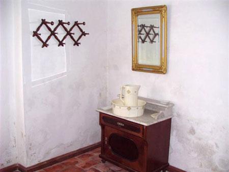 Nizka omarica z marmornato ploščo, porcelanastim umivalnikom in vrčem v veži