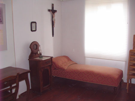 Spalnica s posteljo, omarico in razpelom