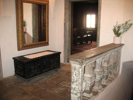 Veža v nadstropju s staro skrinjo in kamnito stebričasto ograjo;