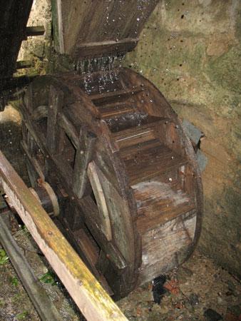 Mlinsko kolo z rako, iz katere pada voda in poganja mlin.