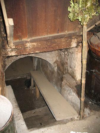 Iz črne kuhinje vodijo strme stopnice v obokano klet