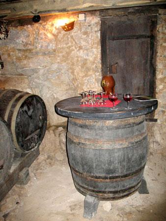 Vinska klet s sodom,  ob katerim obiskovalci poskusijo vino in vrati, ki vodijo v kuhinjoVinska klet s sodom,  ob katerim obiskovalci poskusijo vino in vrati, ki vodijo v kuhinjo