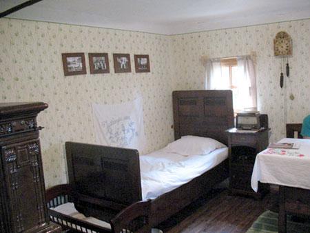 Hiša z ozko zakonsko posteljo, zibelko in starimi družinskimi fotografijami na steni