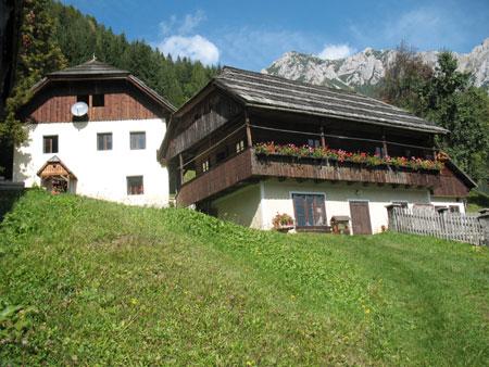 Kašča in preužitkarska hiša z vrhovi Pece v ozadju