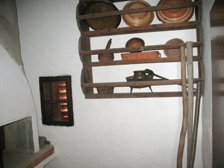 Kurišče z majhnim okencem in skledjakom v majhni črni kuhinji
