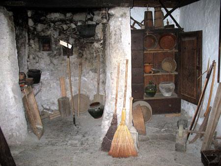 Črna kuhinja s pregrado in številnimi orodji ter kuhinjskimi pripomočki na obeh straneh;