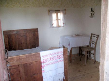 Bivalni prostor v starejšem hisu s skromno opremo.