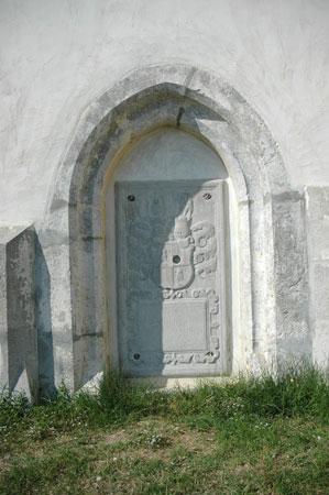 Nagrobni kamen, vzidan v cerkveno fasado