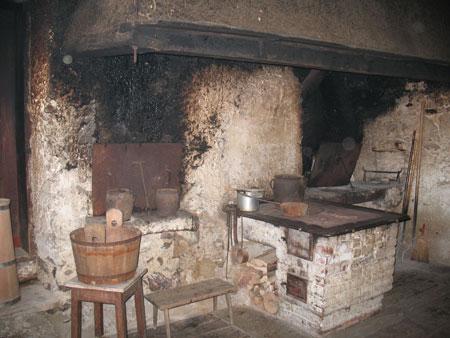 Črna kuhinja z dvema kuriščema, zidanim štedilnikom in veliko napo