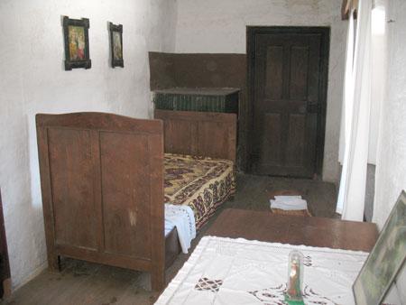 Kamra z manjšo pečjo, posteljo, zibko in skrinjo.