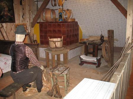 Delovna polovica bivalnega prostora v kmečki hiši v zimskem času, s pečjo kot osrednjim elementom;