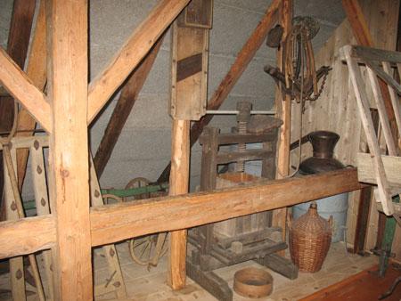 Del zbirke kmečkih orodij in naprav (brana, stiskalnica, kotel itd.), razstavljenih v etno hiši;