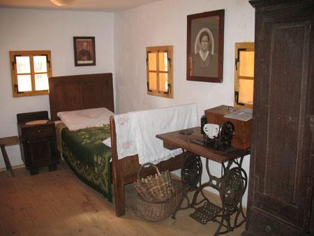 V drugem kotu na vzhodni strani hiše stoji postelja z omarico in šivalnim strojem