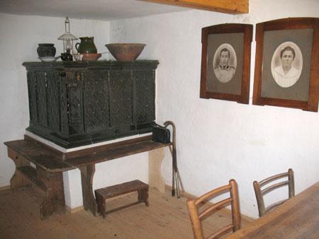 Lončena krušna peč s klopjo v kotu za vrati in nekaj zanimivimi predmeti na njej.