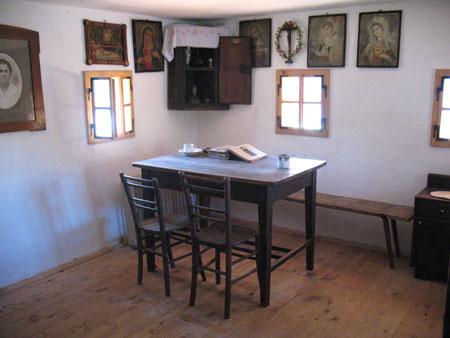 Miza v hiši s klopjo, stoli in nabožnimi slikami v kotu nad njo